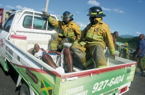 Fire personnel transport an injured man to the May Pen hospital, following an accident along the Bustamante Highway in Clarendon yesterday. The man was driving a Nissan Sunny motor car when it collided with a Leyland Freighter motor truck. (Photo: Llewellyn Winter/Jamaica Observer)