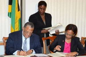 Signing our future away: Finance and Planning Minister, Dr. the Hon. Peter Phillips (left), and Inter-American Development Bank (IDB) Country Representative in Jamaica, Therese Turner-Jones sign copies of two loan agreements for the IDB's provision of just over $15 billion (US$140 million) in budgetary support to the government to undertake the country's Fiscal Structural Programme for Economic Growth, and Competitiveness Enhancement Programme (III). The signing took place on February 6. Overseeing the proceedings is the Ministry's Communications and Public Relations Director, Cheryl Smith. (Photo: Jamaica Information Service)