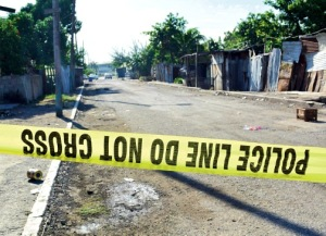 Yellow tape cordons off a crime scene in the salubrious and unsuitably named Majesty Gardens, after a double murder in the area - which is represented by our Prime Minister Portia Simpson Miller. (Photo: Jamaica Observer)