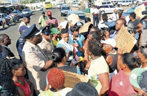 Senior Superintendent of Police Steve McGregor (left) listens to residents yesterday as they protest the death of a detainee in the Darling Street Police lock-up in West Kingston. (Photo: Jamaica Observer)