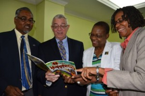 Education MinisterRonald Thwaites (second left), along with Director of Production at the Jamaica Information Service and Civil Servant of the Year, Enthrose Campbell (second right), and co-authors and Co-Founders of Choose Life International Faith Thomas (right), and Dr. Donovan Thomas, peruse a copy of the book, 'H is for Happiness', at a breakfast held in New Kingston on February 7. (Photo: JIS)
