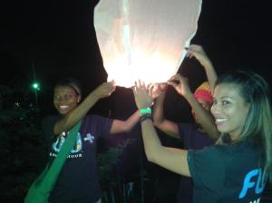 Representatives of the telecoms firm Flow, together with Rootz Underground singer Stephen Newland (hidden, in the middle) release a lantern at the end of the Earth Hour acoustic concert in Kingston.