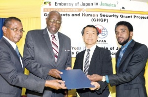 Health Minister Dr Fenton Ferguson (second left) participates in the symbolic presentation of a $123-million (US$117,176) grant agreement being provided by the Government of Japan to the Bustamante Hospital for Children for the acquisition of vital medical equipment, following Wednesday's signing ceremony at the institution. Also participating are the hospital Chief Executive Officer Anthony Wood (left); Chargé d'Affaires at the Japanese Embassy in Jamaica Koji Tomita (second right); and the South East Regional Health Authority's acting chairman, Dr Andrei Cooke. (PHOTO: JIS)