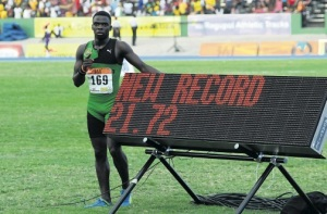Calabar High School's Class Three sprint king Tyreke Wilson poses beside the display board showing his impressive new record achieved in the 200m. (Photo: Jamaica Observer)