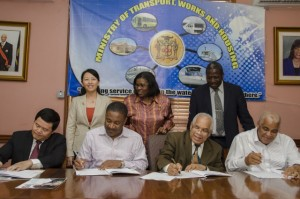 Minister of Transport, Works and Housing, Dr. the Hon. Omar Davies (3rd left), signs a Memorandum of Understanding (MOU), with China Engineering Company (CHEC) for a feasibility study on the damming of the Bog Walk Gorge, at the Ministry in Kingston, on March 28. Also participating are (from left): Ambassador of the People's Republic of China in Jamaica, Mr. Xiaojun Dong; Minister of Science, Technology, Energy and Mining, Hon. Phillip Paulwell; and Minister of Water, Land, Environment and Climate Change, Hon. Robert Pickersgill. In the back row (from left) are: Commercial Counsellor at the Embassy of the People's Republic of China, Mrs. Lei Liu (left); Permanent Secretary in the Ministry of Transport, Works and Housing, Mrs. Audrey Sewell and Permanent Secretary in the Ministry of Water, Land, Environment and Climate Change, Dr. Alwin Hayles. (Photo: JIS)