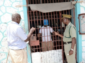 Free at last! Superintendent Rudolf Edwards (right) of the Tamarind Farm Adult Correctional Centre seems quite pleased as he joins Gillette Ramsay (left), a volunteer with Food for the Poor Jamaica, in sharing the good news with one of the three inmates. (Photo: Gleaner)