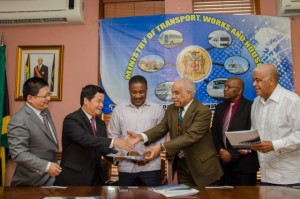 Minister of Transport, Works and Housing, Dr. the Hon. Omar Davies (4th left), presents Memorandum of Understanding (MOU) to Ambassador of the People's Republic of China in Jamaica, Mr. Xiaojun Dong (2nd left), after signing the document with China Engineering Company (CHEC) for the development of a transshipment hub in the Portland Bight and a feasibility study on the damming of the Bog Walk Gorge, at the Ministry in Kingston, on March 28. Sharing in the occasion are (from left): General Manager of CHEC, Mr. Zhongdong Tang; Minister of Science, Technology, Energy and Mining, Hon. Phillip Paulwell; Minister with responsibility for Housing, Hon. Dr. Morais Guy, and Minister of Water, Land Environment and Climate Change, Hon. Robert Pickersgill. (Photo: JIS)