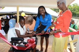 A joyful ribbon-cutting! Sandy Wallace, Resident at Jacob's Ladder is embraced by a Mustard Seed Community  volunteer as she cuts the ribbon for the official opening of the Care Plus Centre of Excellence on Wednesday, March 26. Joining her is Judine Hunter (left), Programme Manager, Special Needs, Digicel Foundation and Thyra Heaven, Board Member, Mustard Seed Communities. Care Plus Centre of Excellence, equipped with rehabilitative and therapeutic facilities, was erected as part of the Foundation's 10th Anniversary goals, to build 10 Centres of Excellence for Special Needs schools across the island this year. (Photo: Digicel Foundation)