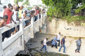 A crowd watches from the bridge on Shortwood Road in Kingston as undertakers and police take Constable Davian Thompson's body from the gully yesterday morning. Police believe the cop committed suicide after killing his wife Saturday night. (Photo: Jamaica Observer)