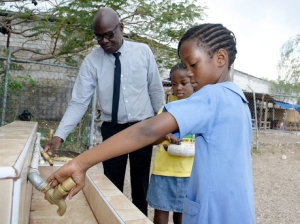 Noel Watt, principal of Dunrobin Primary School, along with students Kelsie Spaulding (left) and Kayla Spaulding, didn't get a drop of water from these pipes at the school yesterday. - (Photo: Gladstone Taylor/Gleaner)