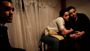 Roma families like the Baloghs have left Hungary in droves in the hope of finding freedom from persecution in Canada. Claudia Balogh, middle, hugs a relative, as her husband Miklos, left, looks on in their home in Budapest on Oct. 22, 2012. (Ed Ou/Reportage by Getty Images for CBC)