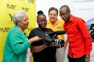 (L) Mrs Marjory Kennedy, Honorary Consul of Australia to Jamaica, Mr Joseph Matalon, Chairman of YUTE Ltd and Mr Tyrone Wilson, President and CEO of eMedia Interactive Ltd are impressed with the budding film skills of Terry-Ann Carnegie, participant in the YUTE Lens Support Program. The program is a joint partnership between Youth Upliftment Through Employment (YUTE) Ltd and eMedia Interactive, through part sponsorship of the Australian High Commission's Direct Aid program. It will facilitate the training of 40 young people in film production. The project was launched on Friday, April 25 at the Technology Innovation Centre, UTech.