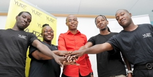 Mr Tyrone Wilson, President and CEO of eMedia Interactive Ltd, (Centre) and YUTE Ltd participants join hands in support of the YUTE Lens Support Program which was launched on Friday, April 25 at the Technology Innovation Centre, UTECH. Through this program which is sponsored in part by the Australian High Commission's Direct Aid program, 40 participants will be trained in film production.