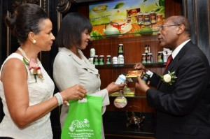 Prime Minister the Most Hon. Portia Simpson Miller (centre), takes a closer look at a bottle of supplements on display inside the herbal and gift store at the Eden Gardens Wellness Resort and Spa, as Executive Chairman, Dr. Henry Lowe (right), and his wife Janet, introduce her to more of the shop's offerings. Occasion was the launch of the newly redeveloped and rebranded facility on March 25, at its Lady Musgrave Road location, in Kingston. (Photo: JIS)