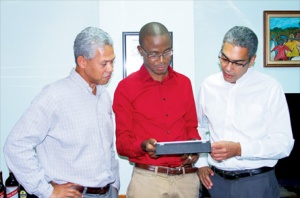 Tyrone Wilson (centre) shows off some of the latest technologies to Sagicor Life president Richard Byles (right) and PanCaribbean CEO Donovan Perkins. Pan Caribbean invested US$350,000 into Wilson's business. (Photo: Jamaica Observer, MARCH 2012)