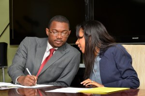Rukiya Brown of the International Organization on Migration (IOM) talks to Minister Arnaldo Brown. (Photo: Jamaica Information Service)