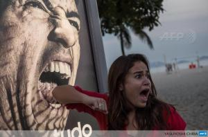 A tourist jokes in front of an advertisement with a portrait of Luis Suarez at Copacabana beach (Photo: AFP)