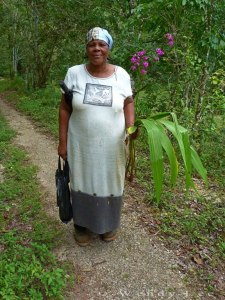 Lady farmer returning from her ground, carrying orchid plants to put in her garden. (Photo: Wendy Lee)