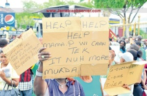 """Protesters placards at Monday morning's protest organized by the Jamaica Labour Party, which some commentators say """"fizzled."""" (Photo: Jamaica Observer)"""