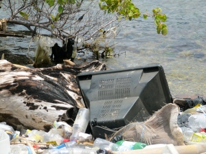 A television set rests among the trash at the Airports Authority of Jamaica's land next to the airport. (My photo)