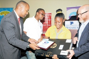 EduFocal Awards 2013: Shamique Francis, the winner in the Grade Six Achievement Test category, accepts her prizes from Julian Robinson (left), minister of state in the Ministry of Science, Technology, Energy and Mining, and Peter Levy (right), managing director of British Caribbean Insurance Company. Sharing in the moment is Gordon Swaby, CEO, EduFocal. (Photo: Naphtali Junior/Jamaica Observer)