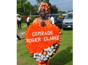 A good comrade: Patricia Williams holds a custom made wreath at former Minister Roger Clarke's funeral, held at the St George's Anglican Church in Savanna-la-mar, Westmoreland on Saturday. (Photo: Janet Clarke/Gleaner)