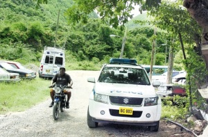 Police vehicles parked in August Town yesterday near where Constable James Grant was shot dead on Monday. (Photo: Michael Gordon/Jamaica Observer)