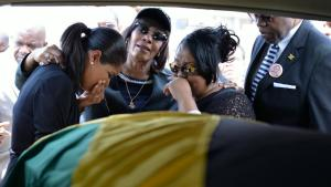 A picture of grief: Youth and Culture Minister Lisa Hanna (left), Prime Minister Portia Simpson Miller (center) and Minister responsible for sports Natalie Neita Headley wept as the body of former Agriculture Minister Roger Clarke arrived at Kingston's Norman Manley International Airport. His funeral will take place on Saturday in Savannah-la-Mar, Westmoreland.