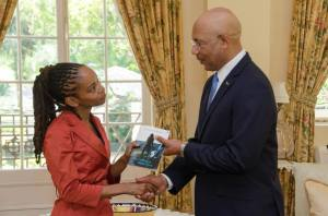 "Jamaican poet Ann-Margaret Lim presented a copy of her book ""Festival of Wild Orchid"" to the Governor General Sir Patrick Allen on October 3."