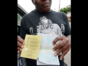 Dr Bob Banjo displays his passport to show that he returned to Jamaica well outside of the 21-day incubation period for Ebola. Banjo also displays a Ghanaian/Nigerian health certificate confirming that he did not have the Ebola virus when he left the region. (Photo: Ian Allen/Gleaner)