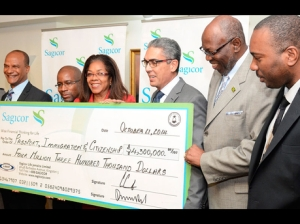 Richard Byles (third right), president and CEO of Sagicor, and Wayne Brown (second left), also of Sagicor, present a cheque to National Security Minister Peter Bunting (left); Jennifer McDonald, CEO of the Passport, Immigration, and Citizenship Agency; Health Minister Dr Fenton Ferguson (second right); and Dr Kevin Harvey, permanent secretary in the Ministry of Health. The funds, handed over during a ceremony at Sagicor's New Kingston head office, are to be used to purchase a fever-scan machine for installation at the Sangster International Airport. (Photo: Gleaner)