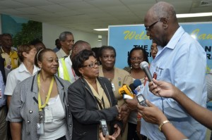 Minister of Health, Hon. Dr. Fenton Ferguson (right), hands over two of four hand-held fever temperature machines that the Government has acquired, to Public Health Nurse attached to the Norman Manley International Airport, Beverly Creary (2nd left), today Friday (October 17), while other medical staff and officials at the Airport, look on. (Photo: Jamaica Information Service)