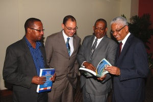 L-R: Professor Ian Boxill, (Carlton Alexander Chair in Management), Don Wehby (GK Ltd Group CEO), Professor Dale Webber (James Moss-Solomon Snr Chair in Environmental Management) and Professor E. Nigel Harris glance through the textbook 'Revista de Biologia Tropical', edited by Prof. Dale Webber during the GKF/UWI Chair Press Conference on November 18, 2014 at the Council Room, UWI Regional Headquarters. (Photo: GraceKennedy Foundation)