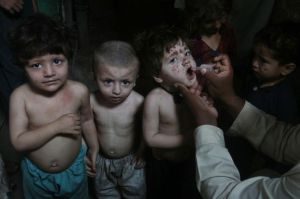 A Pakistani health worker gives a polio vaccine to children in Lahore, Pakistan, Wednesday, June 4, 2014. (AP Photo/K.M. Chaudary)