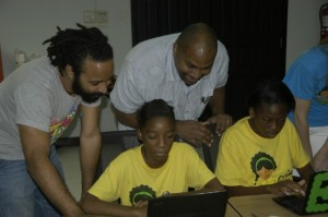 Minister of State in the Ministry of Science, Technology, Energy and Mining, Hon. Julian Robinson (3rd left); and Founder of Halls of Learning, Marvin Hall, seem pleased with Diamond Brown's (2nd left) coding work, during a workshop held recently, at the General Accident Insurance Company's board room in Kingston. At right is workshop participant, Najeeka Rose. (Photo: JIS)
