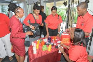 JASL's Nicolette Jones (center) shows some of Life's Work's scented candles to a customer at the World AIDS Day breakfast. (Photo: J-FLAG)