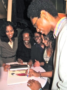 """Nineteen-year-old Mikhail Henry of Glenmuir High School is one of the featured youth photographers in the amazing book """"Take a Look at My World,"""" featuring work from the JN Foundation's Resolution Project. Here he is autographing a page for a group of admiring women. (My photo)"""
