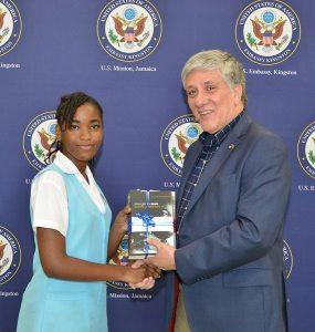 MLK Jr. Essay grand prize winner, Deneve Sweeney of Wolmer's Girls' School in Kingston, receives her gifts from Ambassaor Luis G. Moreno