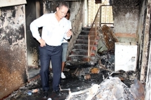 Then Prime Minister and Member of Parliament for West Kingston Bruce Golding visits one of the houses destroyed by fire in Tivoli Gardens during the assault on the area by security forces in May, 2010. (Photo: Jamaica Observer)