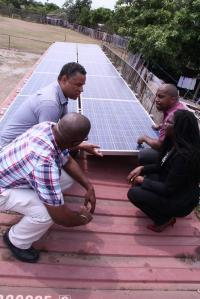 The installation of solar PV panels on the roof of the Jacques Road Computer Centre. On the right is Julian Robinson, the Member of Parliament for the area. (Photo: Twitter)