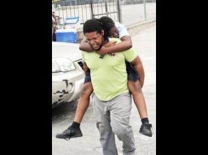 A parent rushes his child who was overcome by smoke to a medical facility. (Photo: Norman Grindley/Gleaner)