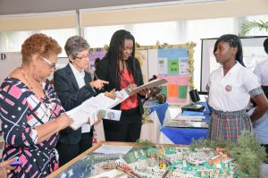 Judges Eleanor Jones (Environmental Solutions Limited), Diana McCaulay, Jamaica Environment Trust and Sharille Pink, speak with a student of Oberlin High School while judging displays on Earth Day, April 22, 2015. (Photo: Jamaica Environment Trust)