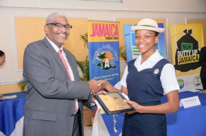 Executive Director of the Tourism Enhancement Fund Clyde Harrison presents the Prize for Best Display (Secondary School) to a member of the Westwood High School team. (Photo: Jamaica Environment Trust)