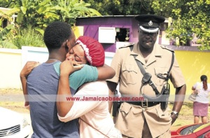 Jacinth Johnson, mother of 12-year-old Shyheim Lewis who was fatally stabbed by his classmate, is comforted yesterday by her spouse Linton White outside the Barrett Town All Age School as Police Superintendent Gary Francis looks on. (Photo: Philip Lemonte/Jamaica Observer)