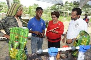 Travis Wilson (2nd left), Level 2 trainee, explains the bamboo manufacturing process to Jean Lowrie-Chin, Chairman, Digicel Foundation on Tuesday, March 31 at the unveiling of the Bamboo Processing Unit, built in partnership with the Digicel Foundation, at the New Horizons Christian Outreach Ministries in Spanish Town. Looking on, from left are Dr. Kadamawe K'Nife, Director, Office of Social Entrepreneurship, UWI and Michael Barnett, Executive Director, New Horizon Christian Outreach Ministries. (Photo: Digicel Foundation)