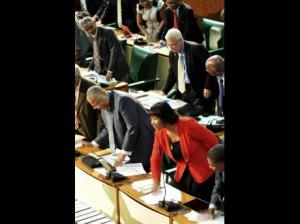 People's National Party Members of Parliament all followed the PM's lead, stood up and thumped their desks after the CCJ bills were passed, while Opposition members sat staring into space. (Photo: Jermaine Barnaby/Gleaner)