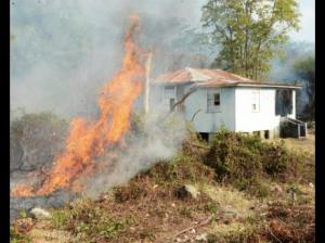 A bush fire threatens this house in Llandewey, western St. Thomas. (Photo: Ian Allen/Gleaner)