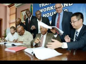 Transport Minister Omar Davies only seems to appear in the media these days when there is an agreement to sign with some Chinese people. Here he is handing the contract for the May Pen to Dawkins Pen road to Xutao Chen (right), general manager for the Jamaica North-South Highway Project, China Harbour Engineering Company Limited. The road is to be rehabilitated under the Major Infrastructure Development Programme. Also signing during the ceremony at the ministry's Maxfield Avenue, St Andrew, offices are James Sampson (left), operations director of S&G Road Surfacing Material Limited; and Rudyard Spencer (second left), member of parliament for South East Clarendon. Assisting in the signing are (from back left) Dr Morais Guy, minister without portfolio in the Ministry of Transport, Works and Housing; Scean Barnswell, mayor of May Pen; and Stephen Shaw, manager of communication and customer services at the National Works Agency. (Photo: Ian Allen/Gleaner)