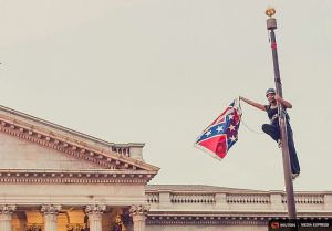 Bree Newsome takes down the flag. (Reuters Media Express/Adam Anderson Photos)