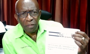 "Jack Warner holding the Onion piece and, as the UK Guardian notes, making himself look ""extremely silly."""
